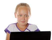 Concept of kids usind unsafe internet surfing. Surprised  girl surfing in internet, over white background Stock Photo