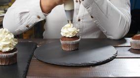 Concept kleine onderneming en Banketbakkerij Vrouwelijke bakker die smakelijke cupcake verfraaien stock video