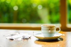 Concept kopkoffie en gescheurd document dichtbij het venster in Th wordt gedronken dat stock afbeelding