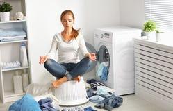 Concept la femme au foyer fatiguée médite en position de lotus dans la blanchisserie photos libres de droits
