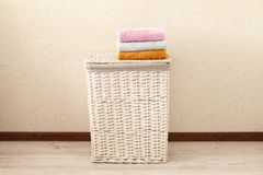 Concept of laundry process. Wicker laundry Basket with colorful towels stock photo