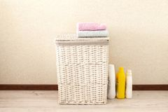 Concept of laundry process. Wicker laundry Basket with colorful towels. On light background stock images