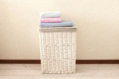 Concept of laundry process. Wicker laundry Basket with colorful towels. On light background stock photos