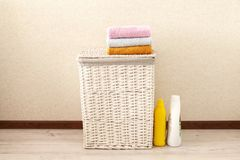 Concept of laundry process. Wicker laundry Basket with colorful towels. On light background royalty free stock photos