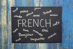 Concept of learning french language. Text written on black paper on wooden background Royalty Free Stock Photos