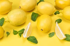 Concept of lemon and its lobules on a yellow. Table stock image