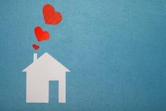 Concept liefde binnenshuis Witboekhuis op blauwe geweven achtergrond met rode harten van pijp Stock Fotografie
