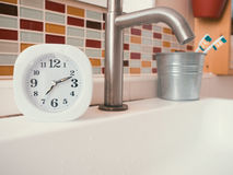 Concept of life routine with clock in the bathroom. Stock Photography