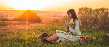 The concept of lifestyle outdoor recreation in autumn. Girl with hat read books on plaid with a thermo cup. Autumn. Sunset. Cozy stock photo