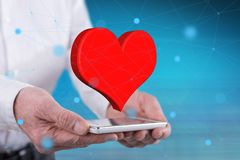 Concept of love. Love concept above a smartphone held by hands royalty free stock photography