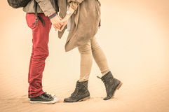 Concept of love in autumn - Couple of young lovers kissing. Outdoors with closeup on legs and shoes - Desaturated nostalgic filtered look Stock Photos