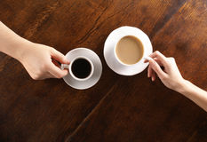 Concept of love and coffee. Concept of male and female hands, love and coffee. Composition taken on a brown wooden table Royalty Free Stock Images