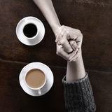 Concept of love and coffee. Concept of male and female hands, love and coffee. Composition taken on a brown wooden table Stock Image