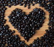 Concept of love with coffee beans. Concept of love with coffee beans on wood texture Royalty Free Stock Photos