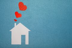 Concept of love in house. White paper house on blue textured background with red hearts from pipe. Stock Photography