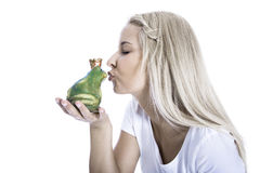 Concept for love: isolated blonde woman is kissing a frog in her Royalty Free Stock Photo