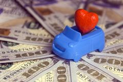 Concept love for money in the car. St. Valentine`s Day. Costs for a honeymoon trip by private transport. Thousand dollars. Red he. Close-up. Red heart in a blue Royalty Free Stock Image