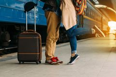 Travel Couple of young lovers kissing outdoors with closeup on legs and shoes. Train station on background. Warm evening royalty free stock images