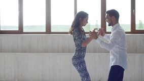 Concept of love, relationships and social dancing. Young beautiful couple dancing sensual dance on a white background. Indoors stock footage
