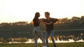 Concept of love and relationships. Young couple dancing at sunset. Concept of love and relationships. Young couple dancing at summer sunset stock video footage