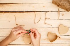 Concept for love stories and for Valentine`s Day. Female hands make boxes in the form of a heart and the inscription `love` from a. Rope. View from above royalty free stock photography
