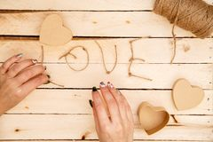 Concept for love stories and for Valentine`s Day. Female hands make boxes in the form of a heart and the inscription `love` from a. Rope. View from above royalty free stock photo
