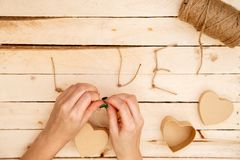Concept for love stories and for Valentine`s Day. Female hands make boxes in the form of a heart and the inscription `love` from a. Rope. View from above royalty free stock image