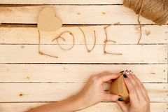 Concept for love stories and for Valentine`s Day. Female hands make boxes in the form of a heart and the inscription `love` from a. Rope. View from above stock photo