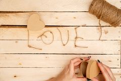 Concept for love stories and for Valentine`s Day. Female hands make boxes in the form of a heart and the inscription `love` from a. Rope. View from above royalty free stock images