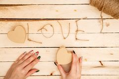 Concept for love stories and for Valentine`s Day. Female hands make boxes in the form of a heart and the inscription `love` from a. Rope. View from above stock photos