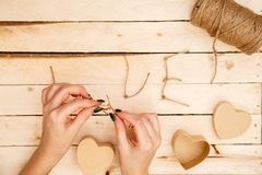 Concept for love stories and for Valentine`s Day. Female hands make boxes in the form of a heart and the inscription `love` from a. Rope. View from above stock image