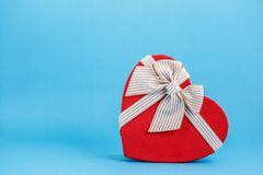 Concept for love stories and for Valentine`s Day. Gift box in the form of a heart on a blue background. front view. stock image
