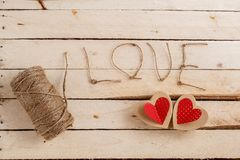 Concept for love stories and for Valentine`s Day. The string, the inscriptions from it and handmade cardboard hearts on a natural stock images