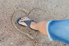 The concept of loveless love and a broken heart. Female foot crushes a heart made of sand