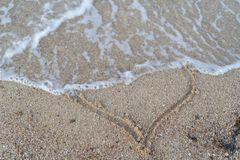 The concept of loveless love and a broken heart. Waves wash off a painted heart