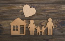 The concept of a loving family. family figure, home, hearts. On a wooden background royalty free stock photography