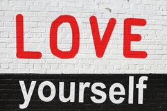 Concept of loving yourself. Written on black and white brick wall royalty free illustration