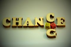 The word CHANCE, CHANGE from wooden letters and two dice of red and yellow on a white background. Concept of luck in the game. Royalty Free Stock Photos