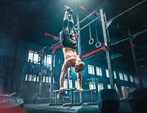 Concept: macht, sterkte, gezonde levensstijl, sport Krachtige aantrekkelijke spiermens bij CrossFit-gymnastiek stock foto's
