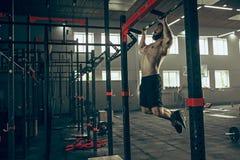 Concept: macht, sterkte, gezonde levensstijl, sport Krachtige aantrekkelijke spiermens bij CrossFit-gymnastiek stock afbeeldingen