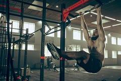 Concept: macht, sterkte, gezonde levensstijl, sport Krachtige aantrekkelijke spiermens bij CrossFit-gymnastiek royalty-vrije stock fotografie