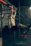 Concept: macht, sterkte, gezonde levensstijl, sport Krachtige aantrekkelijke spiermens bij CrossFit-gymnastiek royalty-vrije stock afbeeldingen