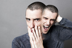 Concept of madness, schizophrenia, mad bipolar behavior and anxiety. With two-headed disturbed man screaming or expressing fear, grey background Stock Photography
