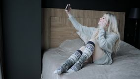 Concept make a selfie. Dreamy Beautiful blonde woman sitting on the bed with smart phone. Girl smiles, good mood. Blogging, browsing internet, chatting. In a stock video footage