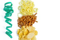 Concept of making choice of food. Unhealthy food: chips, cpackersonion rings vs measuring tape, flat lay. stock images