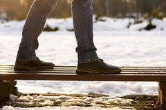 Concept of making decision, beggining, loneliness. Closeup male legs in brown boots and blue jeans are standing on wooden bench in stock photography