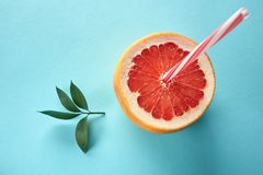 Half a grapefruit in the form of a glass with a drinking tube and a green leaf on a blue background. The concept of making natural juices and cocktails from Stock Image