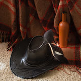 Concept of male and female relationships. Men's Hat, women's shoes, a bottle of wine on the carpet Stock Photo