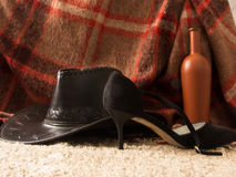 Concept of male and female relationships. Men's Hat, women's shoes, a bottle of wine on the carpet Stock Images