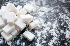 Concept malsain de nourriture - sucre et farine sur un fond noir Images stock